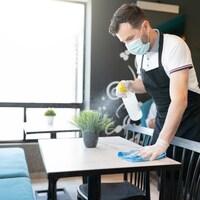Un serveur nettoie une table.