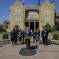 Jason Kenney au podium devant ses ministres.