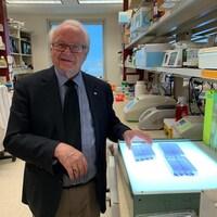 Un homme âgé se situe dans un laboratoire médical. Il tient un récipient en plastique posé sur une table lumineuse.