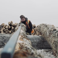 Lydia Petiquay regarde la courbe du billot de bois.