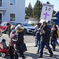 """Dans un manifestation, un manifestant tient une pancarte sur laquelle on peut lire """"Nuremberg 2.0""""."""