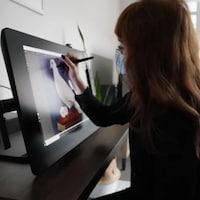 La Dre Marisa Azad crée une œuvre sur une tablette graphique.