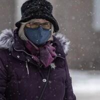 Une femme portant un masque marche dehors pendant qu'il neige.
