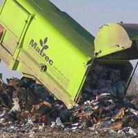 Un camion de transport des déchets vide son contenu dans un site d'enfouissement.