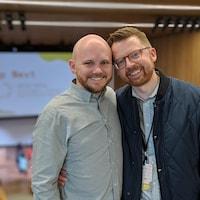 Deux hommes se tiennent côte à côte et sourient à la caméra. L'un est chauve et porte une chemise. L'autre a des lunettes et porte un blouson.