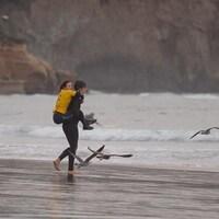 Une femme porte une surfeuse sur ses épaules.