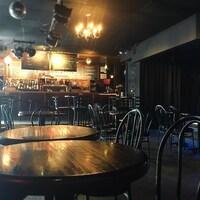 Vue intérieure d'un bar avec plusieurs tables vides et une scène.