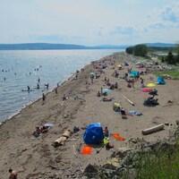 Des gens profitent du beau temps et de la plage.