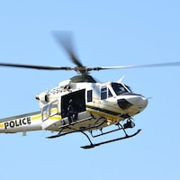 Un hélicoptère de la Sûreté du Québec dans le ciel.