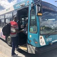 Un homme portant le masque monte à bord d'un autobus.