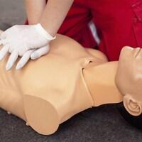 Une personne qui porte des gants pratique la RCR sur un mannequin.