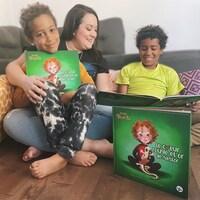 Renee Wilkin et deux jeunes garçons avec plusieurs exemplaires de son livre « Le coeur rouge et or de Nestor ».