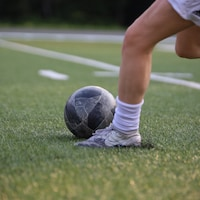 Une jeune femme botte un ballon.