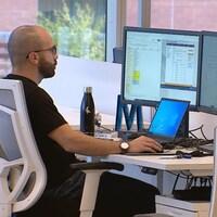 Deux personnes sont assises devant de multiples écrans d'ordinateur.