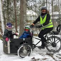 Une femme sourit, assise sur un vélo. Deux enfants sont assis dans un grand panier attaché à l'avant du vélo.
