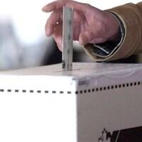 Un bulletin de vote qui est déposé dans une boite de scrutin