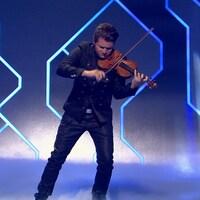 Il joue du violon, la tête penchée, dans un décor futuriste.