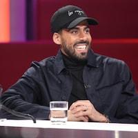 Adib Alkhalidey est à la table des invités. Il porte une casquette, une veste et un chandail noirs.