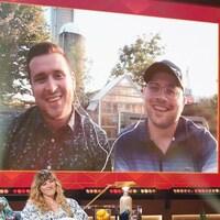 Deux hommes qui sourient. Ils apparaissent sur un écran.