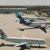 Deux avions d'Air Transat et un d'Air Canada garés sur un tarmac.