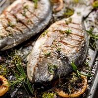 Deux poissons grillés avec du romarin sur une plaque de cuisson.