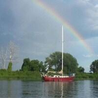 Un voilier sur le fleuve avec un arc-en-ciel.