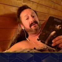 Il est dans son lit, nu, en vidéoconférence, avec un livre à la main.