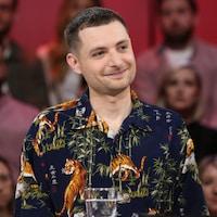 Bernard porte une chemise avec motifs de plantes et de tigres.