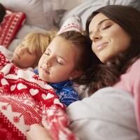 Une famille est endormie dans un grand lit à côté d'un sapin de Noël.
