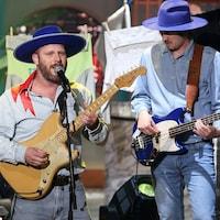 Le groupe joue de la guitare et chante au micro.