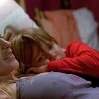 Dans un lit, une femme lit un livre, ses deux enfants allongés contre elle