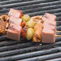 Une brochette sur un grill avec des cubes de viande, des figues, des olives et des légumes grillés.