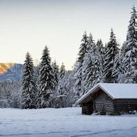 Paysage enneigé au crépuscule, une cabane en bois au premier plan.