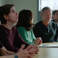 Elle est entourée d'amis et d'intervenants autour d'une table.