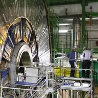 Deux hommes casqués travaillent près de l'accélérateur de particules.