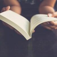 Une personne tient un livre ouvert dans ces mains.