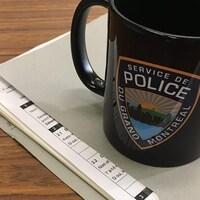La tasse noire de District 31 : Service de police du Grand Montréal.