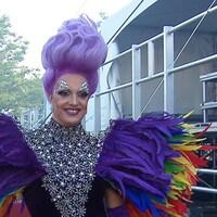 Une drag queen avec des épaulettes surdimensionnées en plumes aux coloris de l'arc-en-ciel et des cheveux violet montés haut sur sa tête. Elle est dans les coulisses du festival de la fierté.