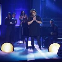 Elle est sur scène entourée de chanteurs et d'un pianiste.