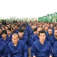 Des prisonniers en bleu dans un camp de détention