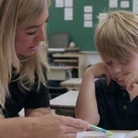 Une enseignant aide un élève à lire.