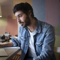 Un homme regarde quelque chose sur son ordinateur portable.