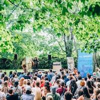 Pomme chante accompagnée de son guitariste Philémon Cimon sur une scène extérieure, entourée d'arbres.