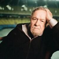 Il est assis dans les gradins du stade Olympique, avec un air triste et songeur.