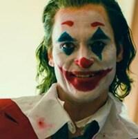 Un homme souriant (Joaquin Phoenix) porte un maquillage de clown.
