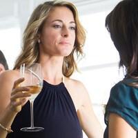 Une femme en robe de soirée, un verre à la main