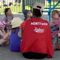 Une monitrice est assise avec un groupe d'enfants et mangent leur lunch.