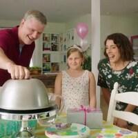 Un père a la main sur la cloche à gâteau pour l'ouvrir pendant que la fillette et la mère sourient, impatientes.
