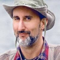 Martin Petit a un chapeau sur la tête et sourit.