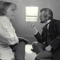 Un médecin parle à un homme au visage difforme, assis sur un lit, en noir et blanc